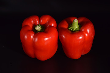Bright red peppers on a seamless black background.