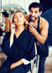 Man makeup artist applying cosmetics for woman talking phone