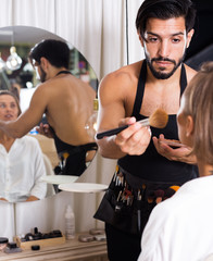 male makeup artist applying cosmetics for female