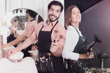 Smiling woman hairdresser and male makeup artist