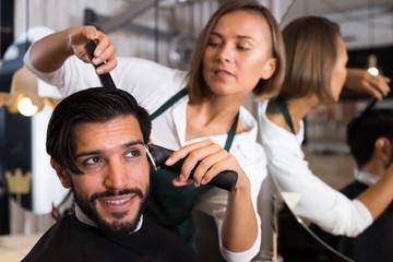 female professional shaving cheerful male's hair
