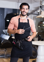 Smiling young worker man hairdresser standing