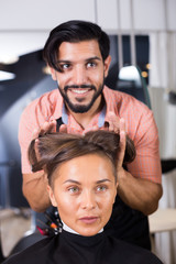 man hairdresser making hairstyle for woman