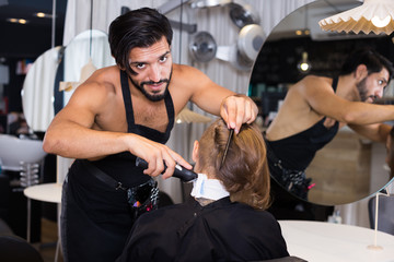 Cheerful male professional shaving female's hair