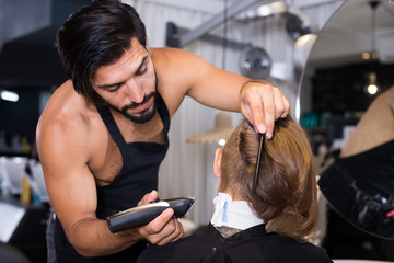 hairdresser working with hair clipper
