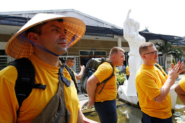 A U.S sailor wears a traditional Vietnamese conical hat during a visit to a hospice for Agent Orange victim as part of the visit to Vietnam of U.S aircraft carrier USS Carl Vinson in Danang