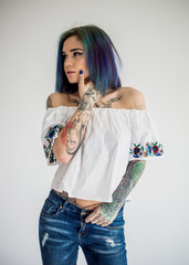 Beautiful woman with colored hair and tattoos in embroidered top posing isolated on white background