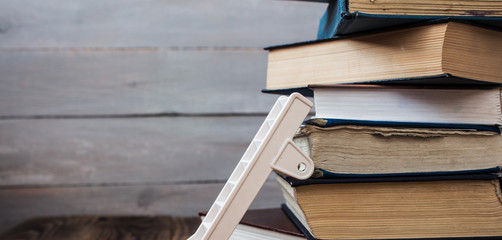 ladder on pile of old books on wooden background
