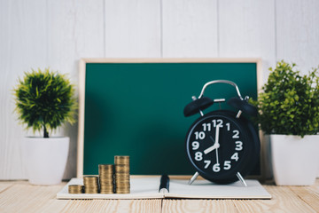 Step of coins stacks and alarm clock with green chalkboard, notebook and financial graph, business planning vision and finance analysis concept.
