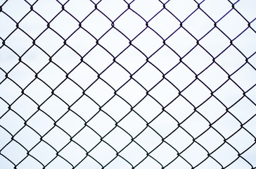 Rusty chain link fence of steel netting on white snow background in cold winter day.