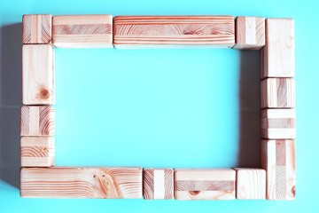 Frame of natural wooden blocks and cubes for photo, picture or slogan of business concept on light blue background. Horizontal top view image with copy space for text.