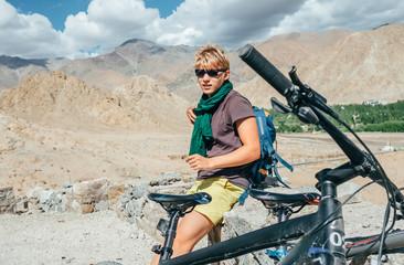 Young man bike traveler rest on high mountain road in Himalaya
