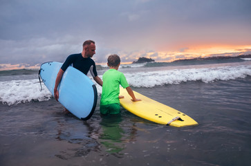 Father learning his son to surf at sunset time