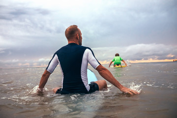 Father and son surfers overcome waves on surf line