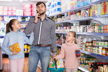 Man speaking phone during shopping with two little girls in grocery store