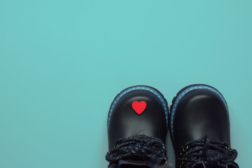 Black kid's winter boots and little wooden heart on bright blue background. Love concept. Father days card.