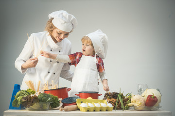 Mom and kid with smiling face cooking spaghetti together.
