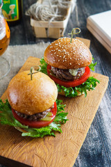 Tasty and appetizing hamburger cheeseburger on a wooden board side view