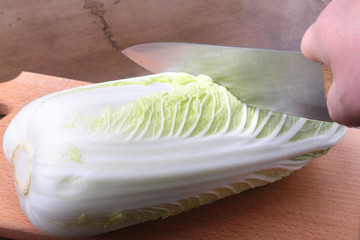 Fresh ripe Chinese cabbage and knife on the cutting board. Ingredients for salad. Ready for cooking.