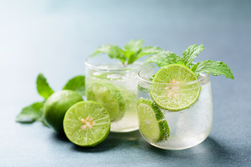 Glass of iced lemonade soda with slice lemon and mint leaves, cold drink in summer