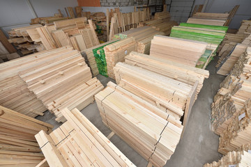 Many folded wooden planks in a warehouse with a forest