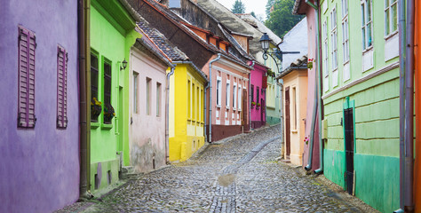 old street with colorful houses in Sighisoara medieval city, Romania