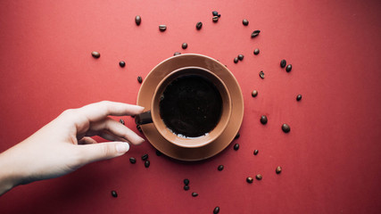Top view of female hand holding cup of coffee
