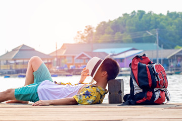 Young man wearing a vintage style shirt and brim hat on face. He waited and sleeping at the pier to travel and relax at the beach with backpack. Soft focus and blur. Tourist concept.