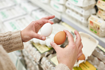 Hands of woman with white and brown eggs in store