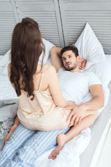 partial view of young man looking at girlfriend in pajamas on bed