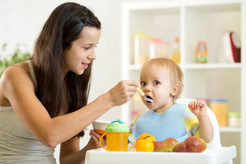 Mom giving homogenized food to her baby son on high chair in kitchen.