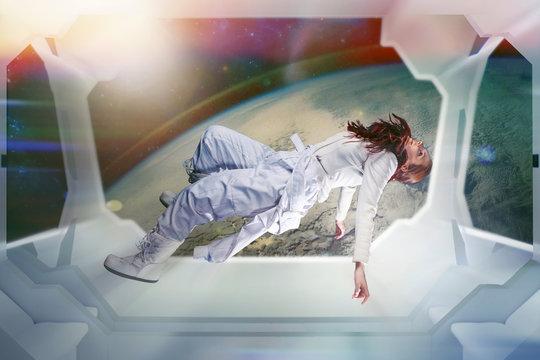 Woman astronaut on a futuristic spaceship. Floating in zero gravity