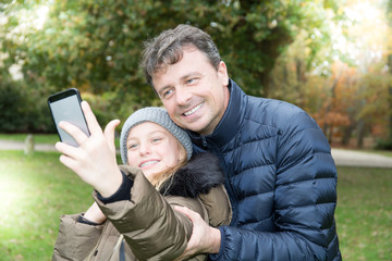 handsome father with cute blonde daughter make selfie in autumn winter outdoor smile and love