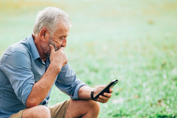 Senior men using a smartphone while sitting on grass in the park