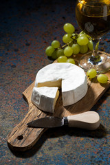 Camembert cheese on a cutting board and a glass of white wine, vertical