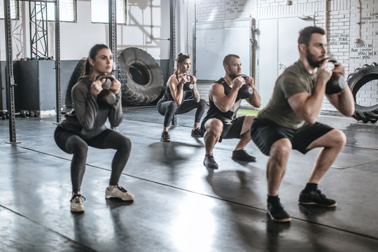 Sportsmen and Sportswomen Lifting Weights at Gym