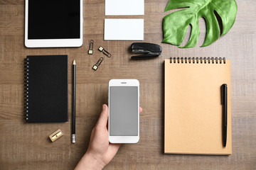 Woman holding phone over table with stationery. Mockup for design