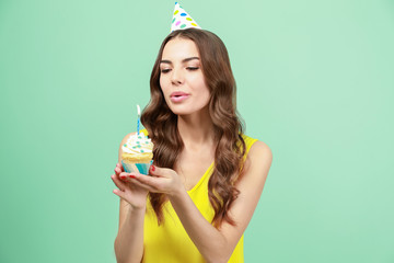 Beautiful young woman snuffing out candle on birthday cupcake against color background