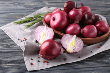 Plate with red onion on wooden table