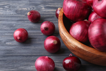 Bowl with red onion on wooden table