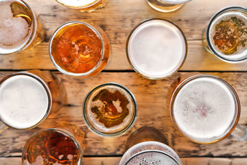 Glassware with fresh beer on wooden background, top view