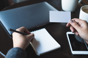 Closeup image of a woman's hands holding empty white business card and writing on blank notebook with laptop and mobile phone on the table