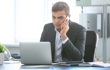 Young man in office wear talking on phone at workplace