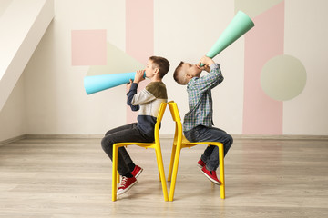 Funny little boys with paper megaphones indoors
