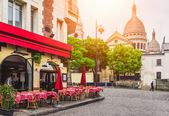 Poster Paris Cozy street with tables of cafe in quarter Montmartre in Paris, France