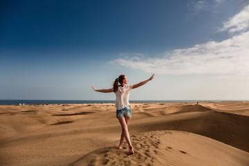 Junge Frau läuftauf dem Sand in Maspalomas