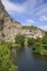 Europe, France, Quercy, Lot, Quaint village houses sit between the cliffs and the River Cele in Cabrerets