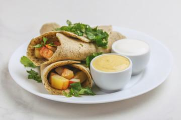 Vegetarian masala dosa with potato, chutney and sambar sauces.