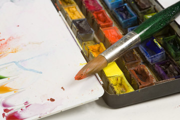 Well used artists watercolour paint palette and paint brushes