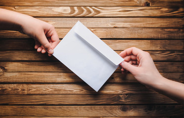 White envelope in the hands of two people on a wooden background. Online donation. The concept of writing. The Internet.